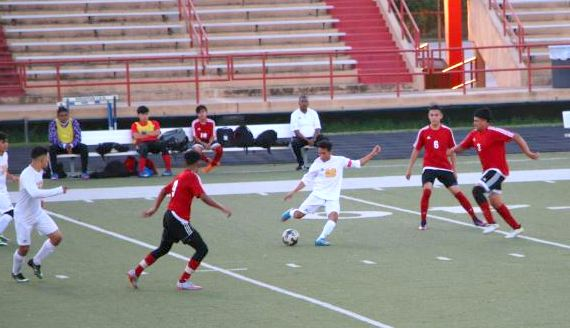 Wisdom's Manuel Flores dribbles the ball through some Waltrip defenders