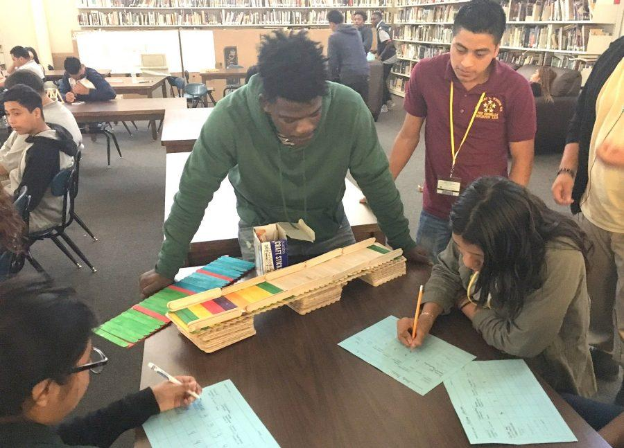 Christopher Basilwabo shows his bridge to journalism students who judged the competition.