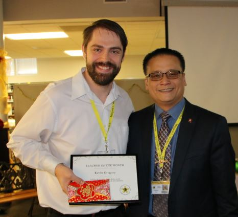 Mr. Gregory receives the December Teacher of the Month Award from Mr. Trinh
