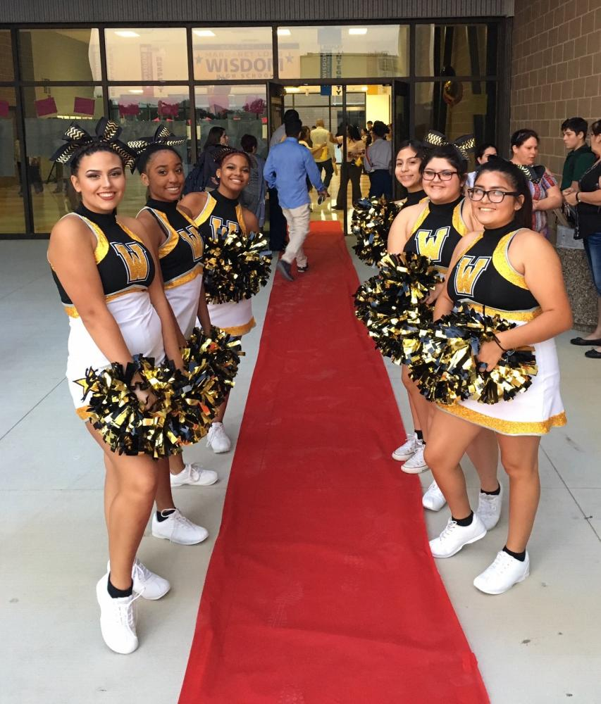 The Wisdom Cheerleaders line a red carpet entrance as students arrive for the first day of classes at the brand new campus.