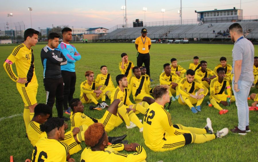 The Wisdom Generals listen to Coach Fidel Andrade at halftime of a recent match