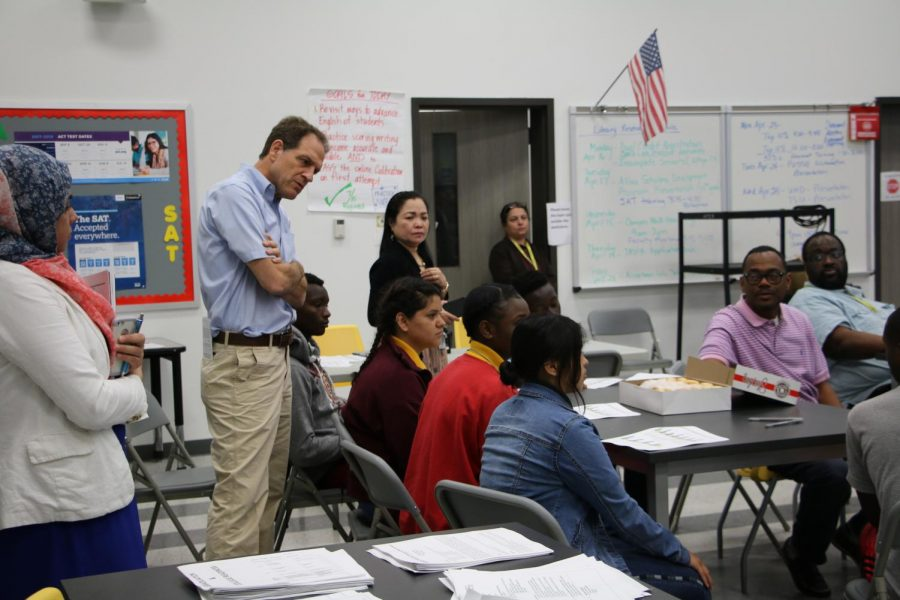 Mr.+Reed+-+an+ESL+Teacher+-+and+others+listen+to+a+student+during+a+recent+community+engagement+event+at+Wisdom+HS.+