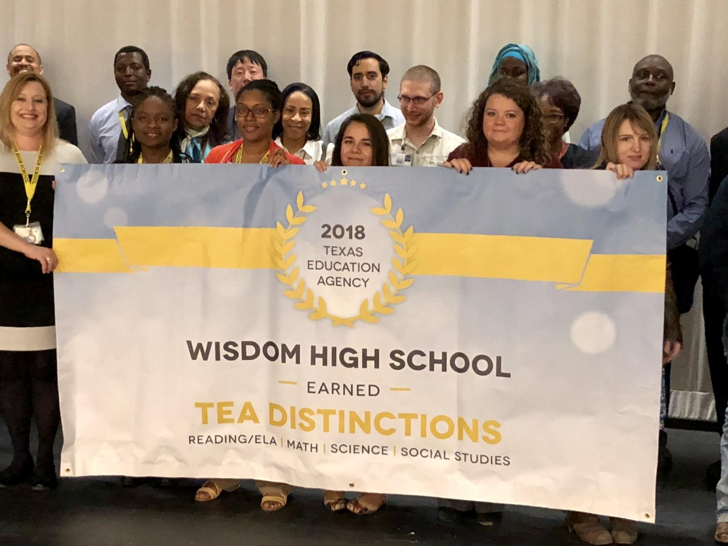 Several Wisdom HS Teachers are shown here holding a banner that features the TEA Distinctions earned by the school for 2018.