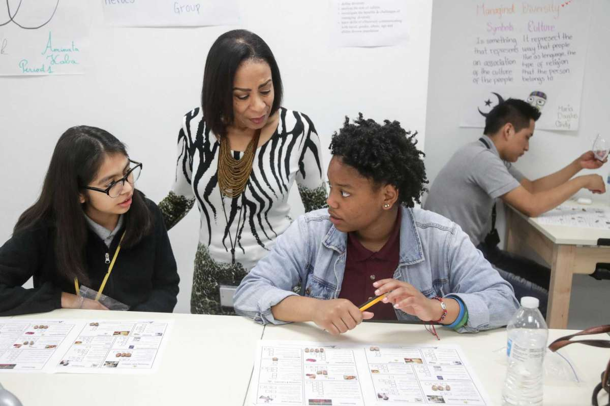 Mrs. Smith speaks with students Eyanni Waterman (right) and Maria Rios (left) during the financial literacy class.