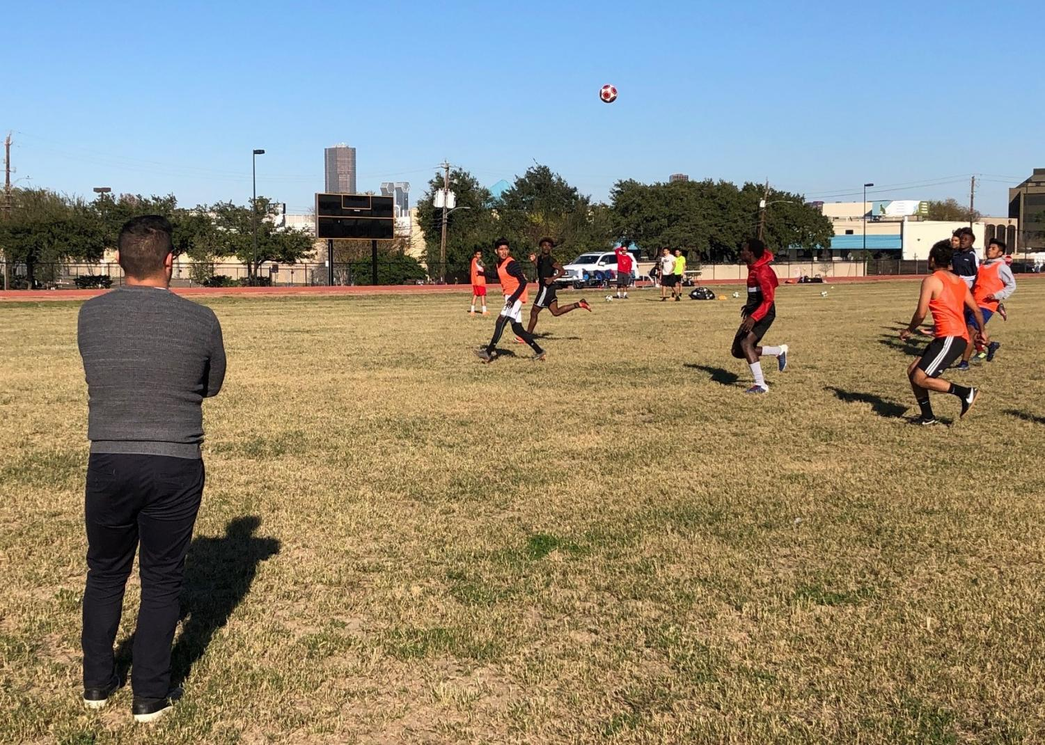 Coach Fidel Andrade watches as his varsity soccer players practice on the new grass field in front of the new Wisdom HS campus building near Richmond & Hillcroft. This is the first season that the Generals have been able to practice on their campus in five years.
